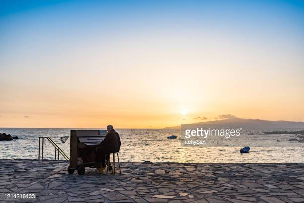 playing a piano in front of the ocean - pianist front stock pictures, royalty-free photos & images