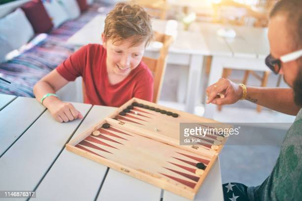 playing backgammon at vacation - backgammon stock pictures, royalty-free photos & images