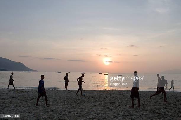 playing beach soccer at sunset on beau vallon beach. - ビーチサッカー ストックフォトと画像
