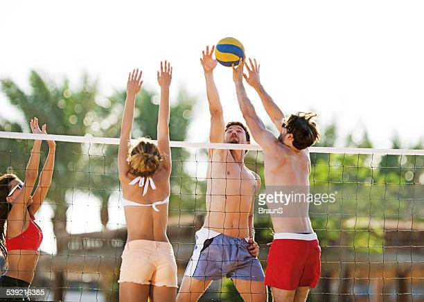 Playing beach volleyball in summer day.