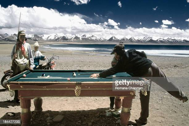 Playing billard on the shores of namtso lake. It is a fouvorite pastime for men in tibet and china alike.the fact that the table is outdoors shows...