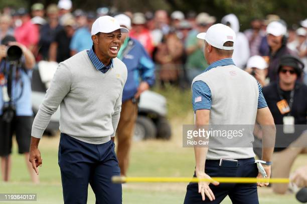 Playing Captain Tiger Woods of the United States team and Justin Thomas of the United States team celebrate defeating ByeongHun An of South Korea and...
