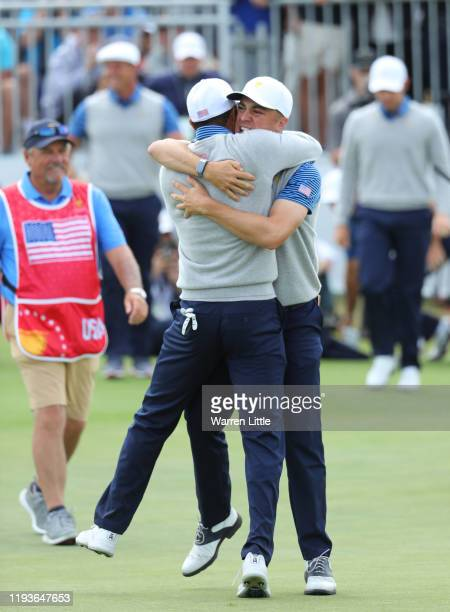 Playing Captain Tiger Woods of the United States team and Justin Thomas of the United States team celebrate defeating Byeong-Hun An of South Korea...