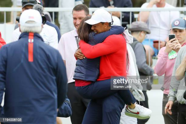 Playing Captain Tiger Woods of the United States team celebrates with girlfriend Erica Herman after defeating Abraham Ancer of Mexico and the...