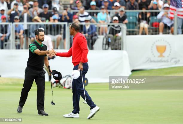 Playing Captain Tiger Woods of the United States team shakes hands with Abraham Ancer of Mexico and the International team after defeating him 32...