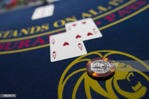 Playing cards and chips are displayed on a blackjack table at the MGM Resorts International casino plays a hand of blackjack with a customer in Las...