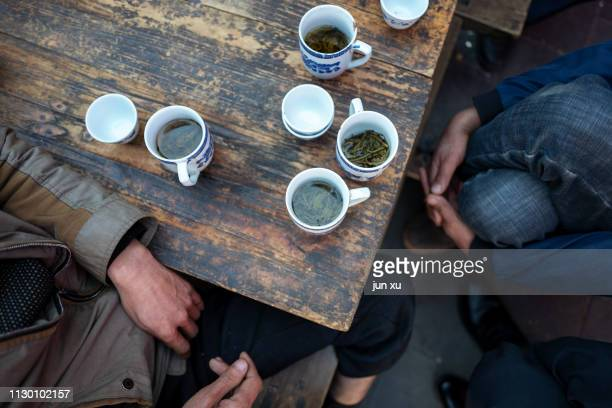 playing cards and drinking tea in a teahouse - tea room stock pictures, royalty-free photos & images