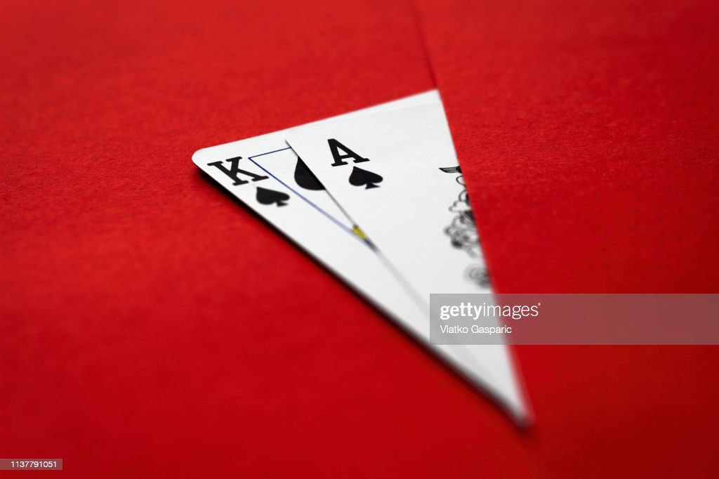 Playing cards, king and ace on red surface : Stock Photo