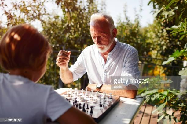 spielen sie schach-großvater-enkel - schach stock-fotos und bilder