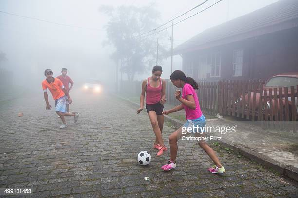 Playing football on a fog covered cobbled street