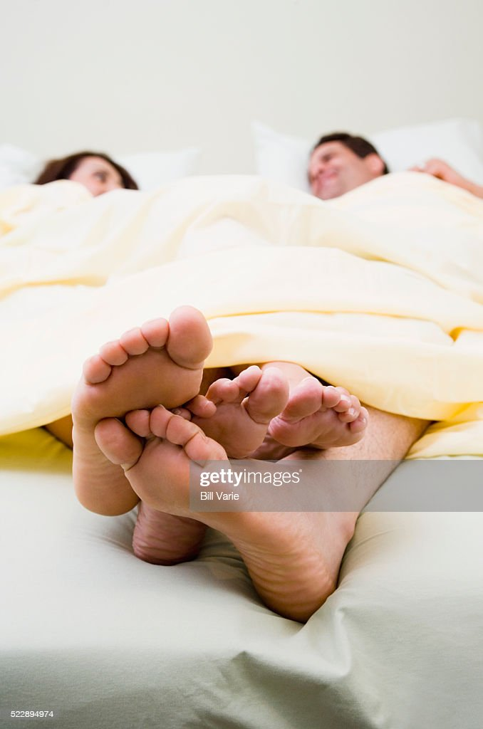 Playing footsie in bed : Stock Photo