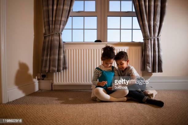 携帯電話でゲームをする - 暖房用ラジエーター ストックフォトと画像