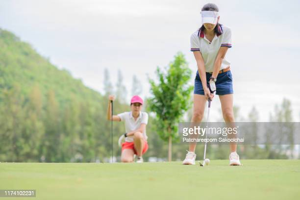 playing golf at course - パットする ストックフォトと画像