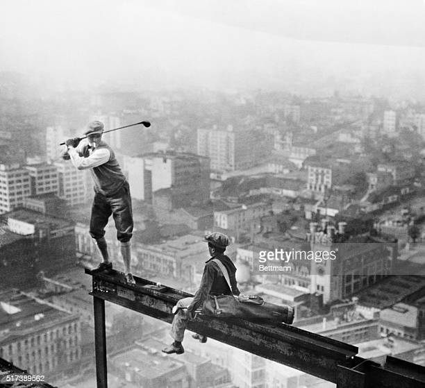 Playing golf in mid-air: Stunts. A cigarette smoking golfer and his caddy teeing off on the girder of a building under construction high over an...