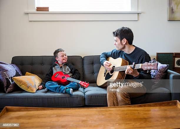 Spielt Gitarre mit Vater auf der couch