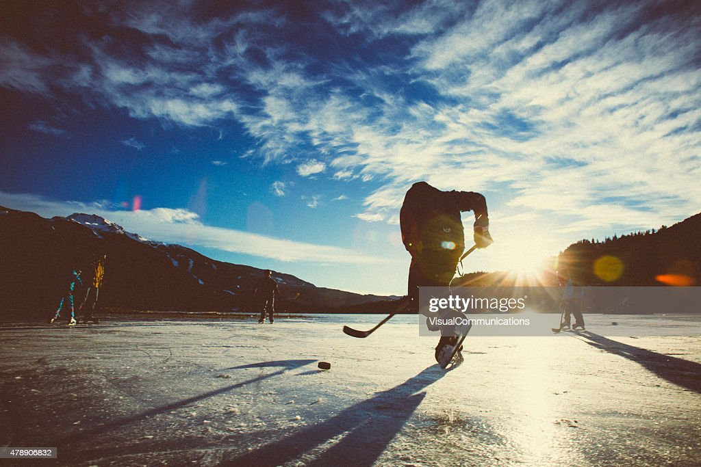 Playing ice hockey on frozen lake in sunset. : Stock Photo