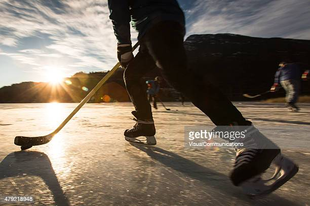 playing ice hockey on frozen lake in sunset. - canadian culture stock pictures, royalty-free photos & images