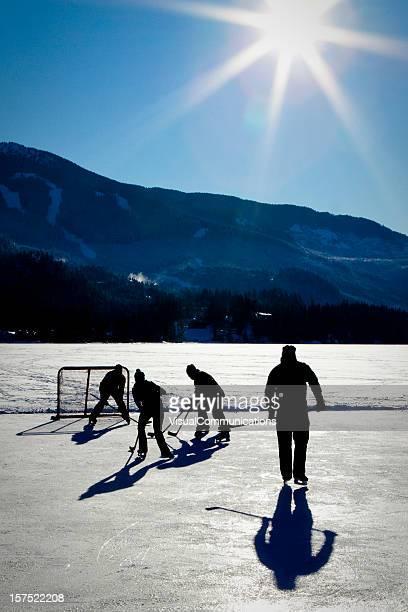 Playing ice hockey on frozen lake.