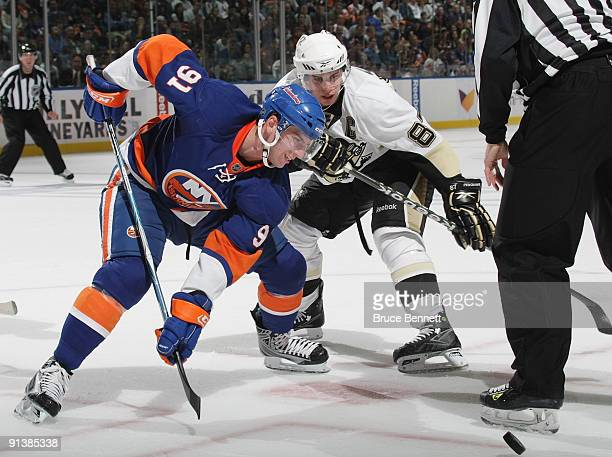 Playing in his first NHL game John Tavares of the New York Islanders skates against Sidney Crosby of the Pittsburgh Penguins at the Nassau Coliseum...