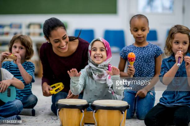 playing instruments - teacher stock pictures, royalty-free photos & images