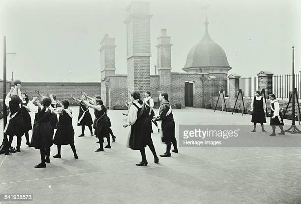 Playing netball, Myrdle Street Girls School, Stepney, London, 1908. Girls play a game of netball on a rooftop playground. Artist: unknown.