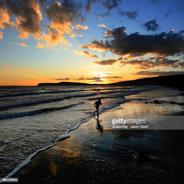 playing  on coast at sunset  - compton bay isle of wight stock pictures, royalty-free photos & images