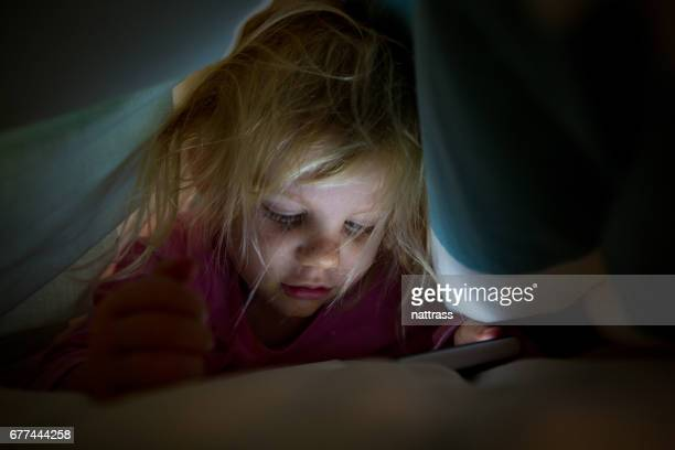 Playing on mobilep phone under the duvet