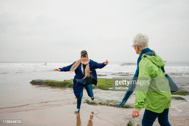 playing on the beach like kids - side by side stock pictures, royalty-free photos & images