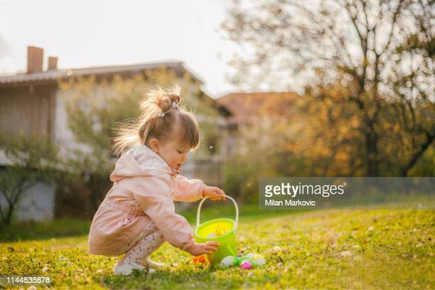 playing on the lawn next to the house during the easter - easter egg hunt stock pictures, royalty-free photos & images