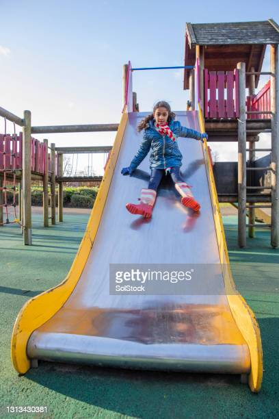 playing on the slide - vertical stock pictures, royalty-free photos & images