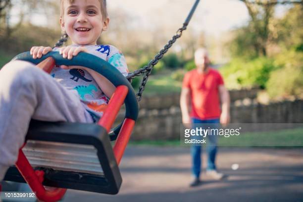 playing on the swings in the park - britain playgrounds stock pictures, royalty-free photos & images