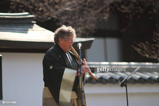 playing shakuhachi at stage - bamboo flute stock photos and pictures