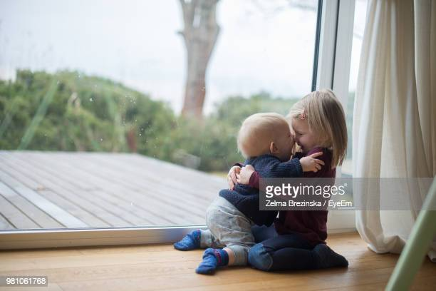 Playing Siblings On Window Sill At Home