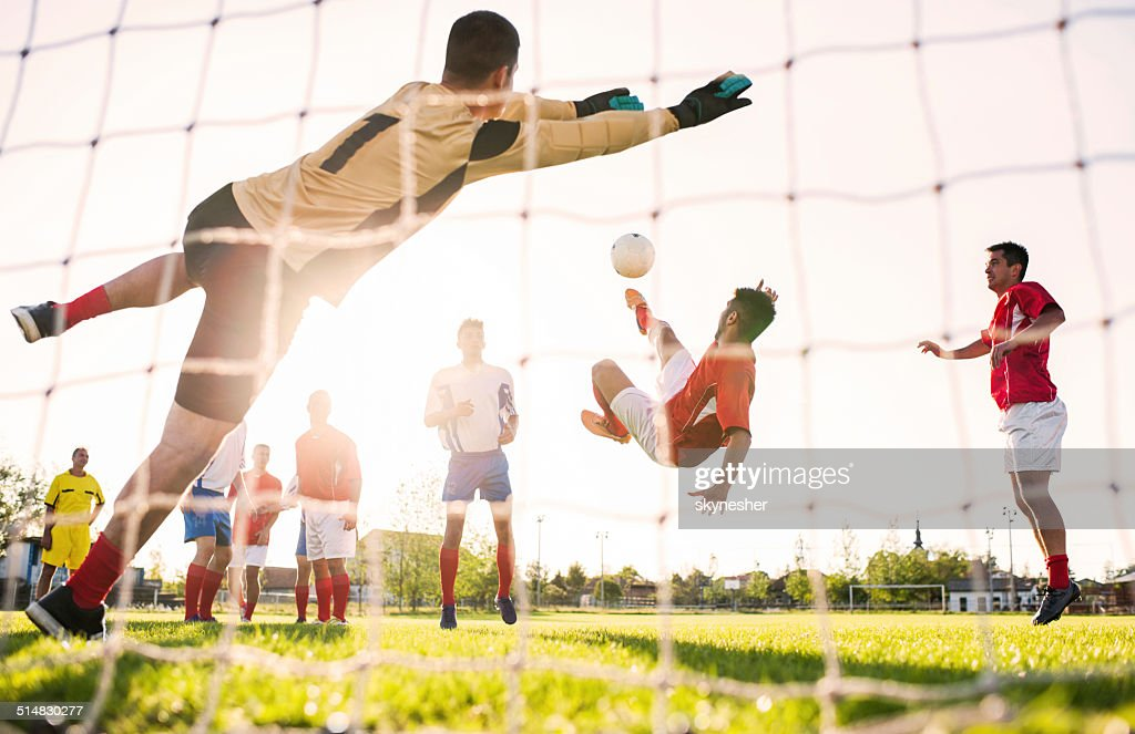 Playing soccer at sunset. : Stock Photo