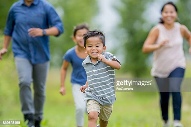 corre que te pillo en el parque  - kids playing tag fotografías e imágenes de stock