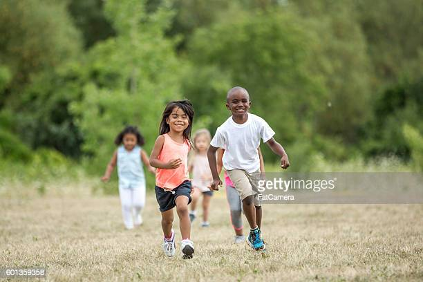 playing tag during recess - kids playing tag stock photos and pictures