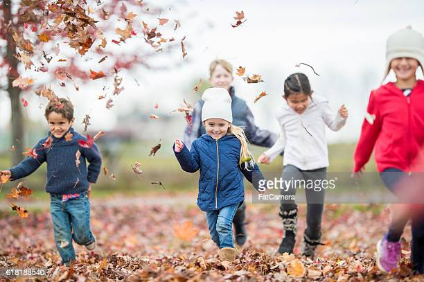 playing tag in fall - kids playing tag ストックフォトと画像