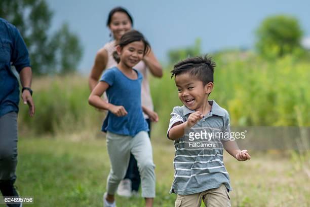 corre que te pillo al aire libre - kids playing tag fotografías e imágenes de stock
