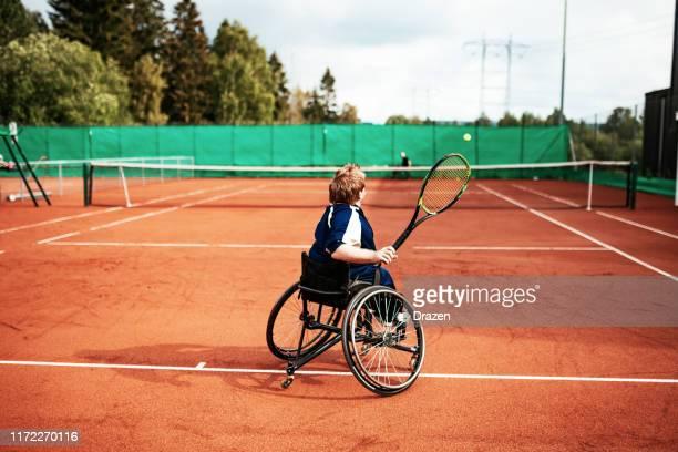 クレーコートで車椅子でテニスをする - 車いすテニス ストックフォトと画像