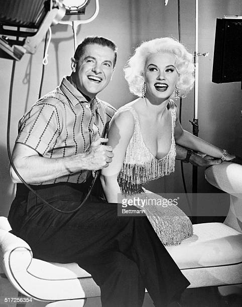 Playing the part of a Bachelor photographer Bob Cummings seems to be enjoying himself as he prepares to snap the shutter on Mamie Van Doren They...
