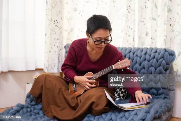 playing the ukulele at home - ukulele stock pictures, royalty-free photos & images