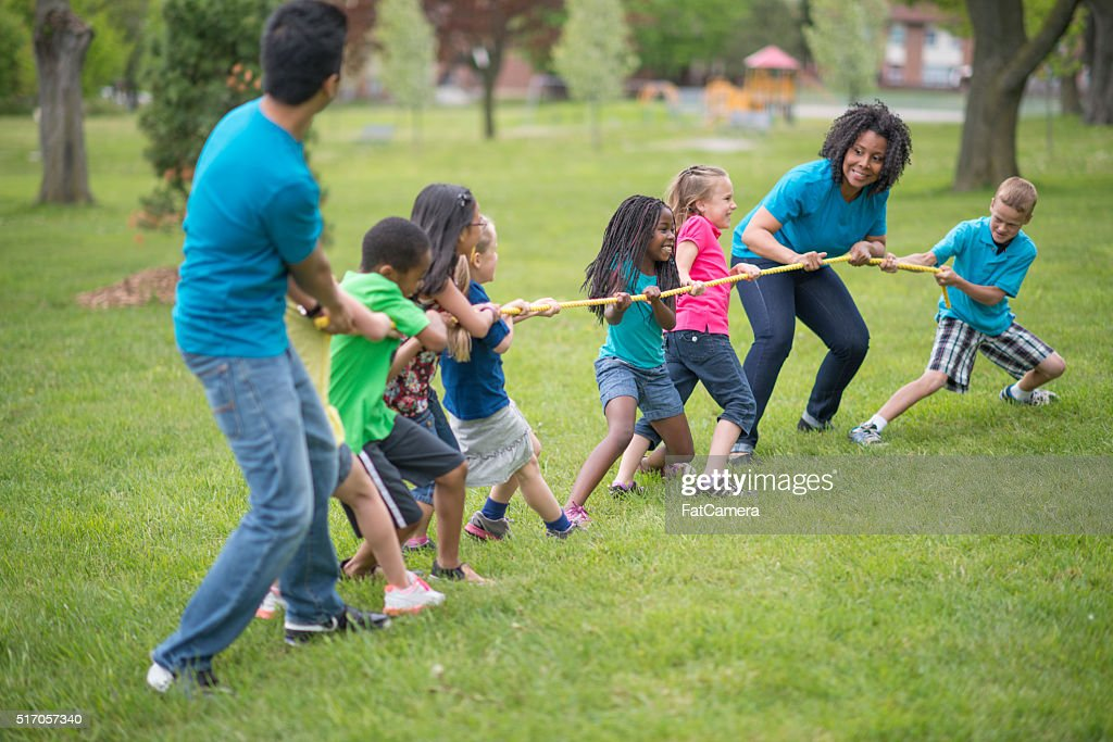 Playing tug-of-war at the Park : Stock Photo