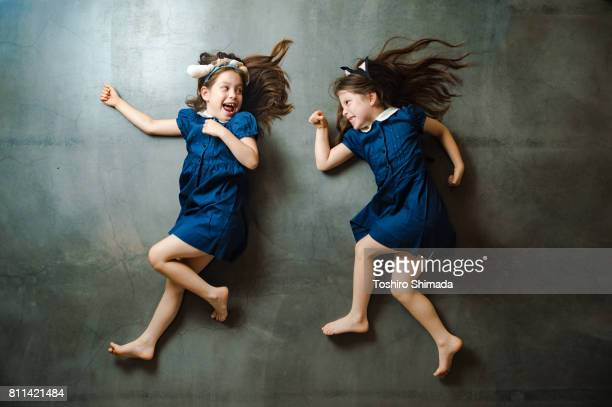 playing twin - lying down stock pictures, royalty-free photos & images