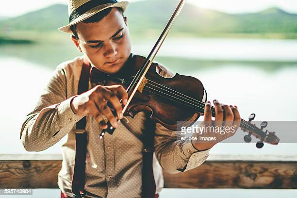 Playing violin by the lake