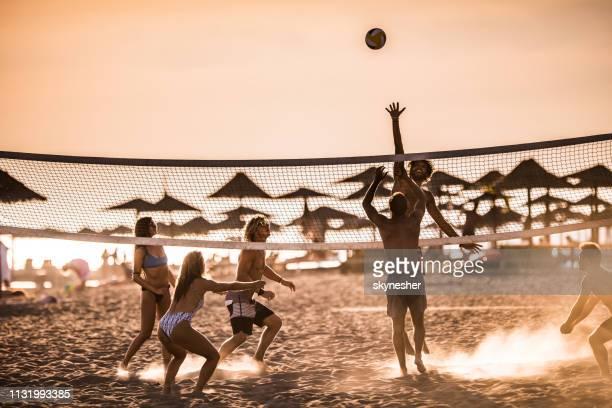 volleyball spielen am strand bei sonnenuntergang! - strand volleyball stock-fotos und bilder