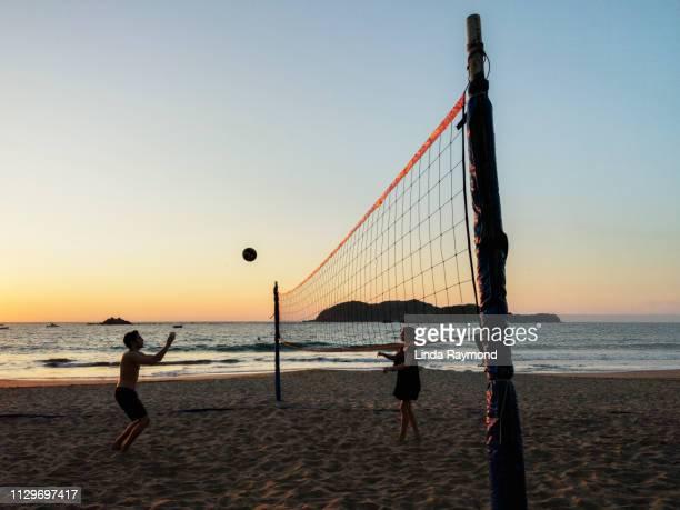 jugando voleibol en la playa - vóleibol de playa fotografías e imágenes de stock