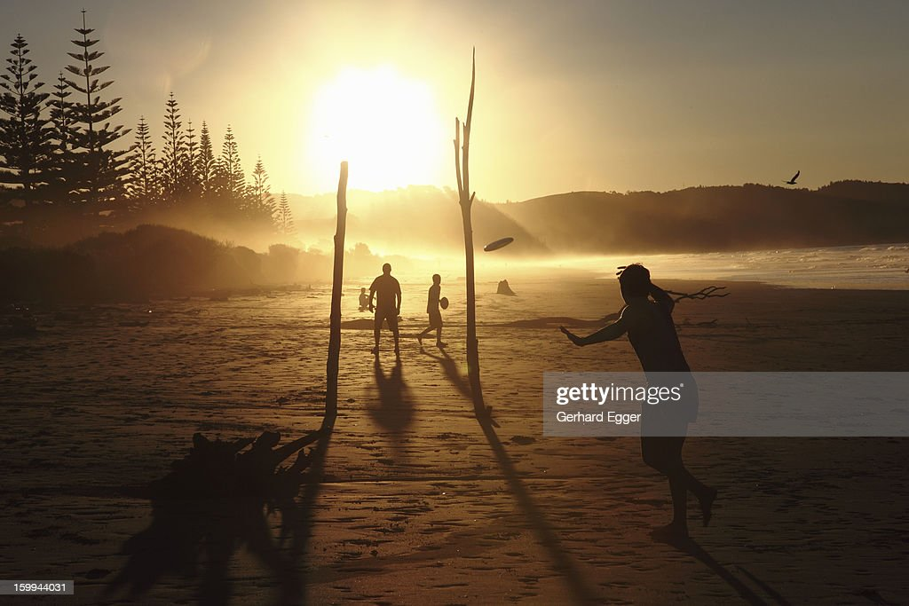 Playing with a frisbee on a beach at sunset : Stock Photo