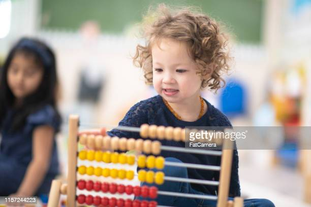 playing with abacus - montessori education stock pictures, royalty-free photos & images