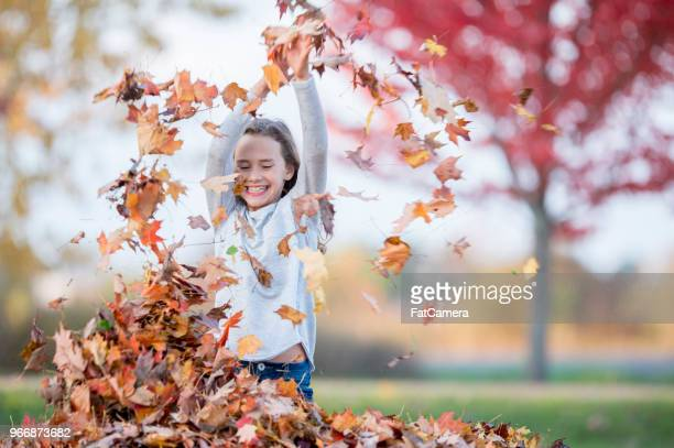 playing with leaves - girl mound stock pictures, royalty-free photos & images