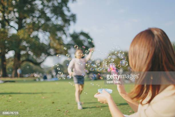 playing with soap bubbles in sunny park - ippei naoi stock photos and pictures